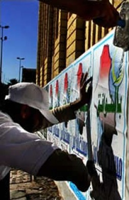 Workers from the Iraqi Islamic Party, made up of Sunni Arabs, pasted posters on a wall in Baghdad recently.