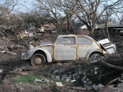 Topsy turvy: VW beetle in the debris infront of damaged houses.