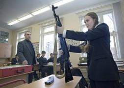 Inna Lyubchenko, 16, disassembling and reassembling a Kalashnikov rifle at Moscow's School No. 1571. Her instructor, Oleg Maslennikov, watches.