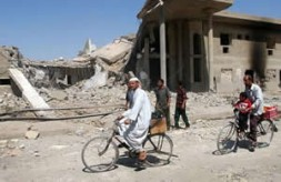 Baqouba residents cycle past a building in Baqouba, Iraq Friday, June 25, 2004, where U.S. warplanes bombarded insurgent positions on…