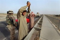 Iraqi men wait to be searched by U.S. Army soldiers at a highway checkpoint near Ramadi, Iraq.