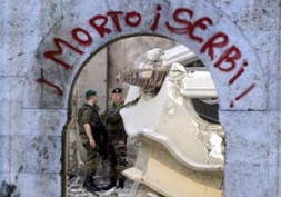 A call for ethnic cleansing in Kosovo at the gate of a destroyed church.